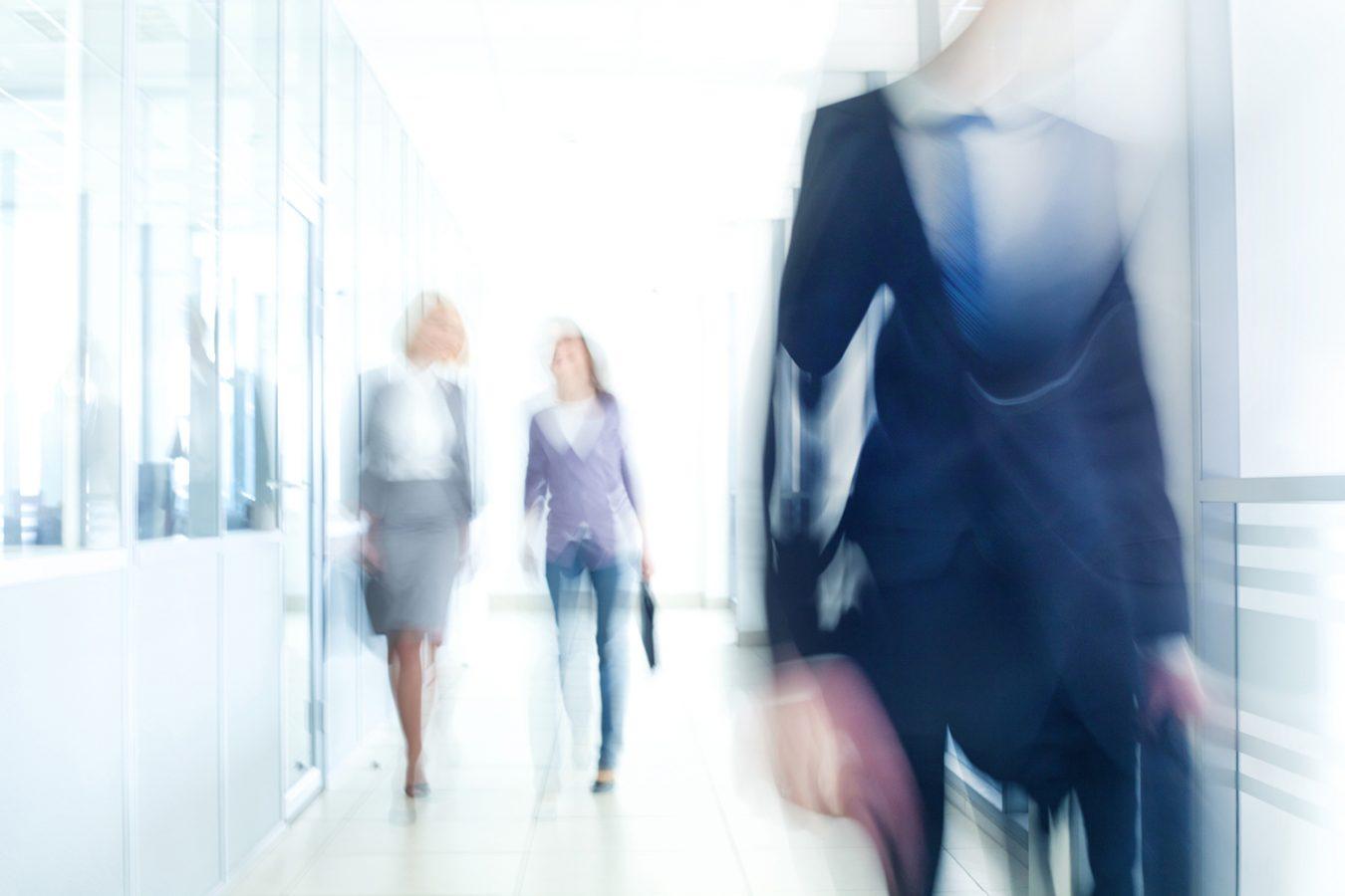 To kvinner og en mann går gjennom en korridor. Bildet er uskarpt.