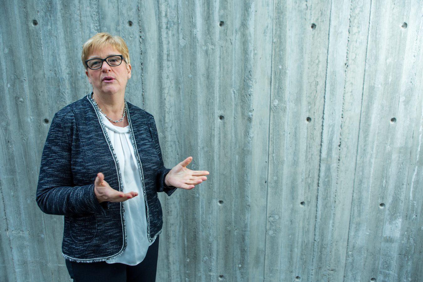 YS-leder Jorunn Berland står foran en grå vegg. Hun snakker, og gestikulerer med åpne hender.