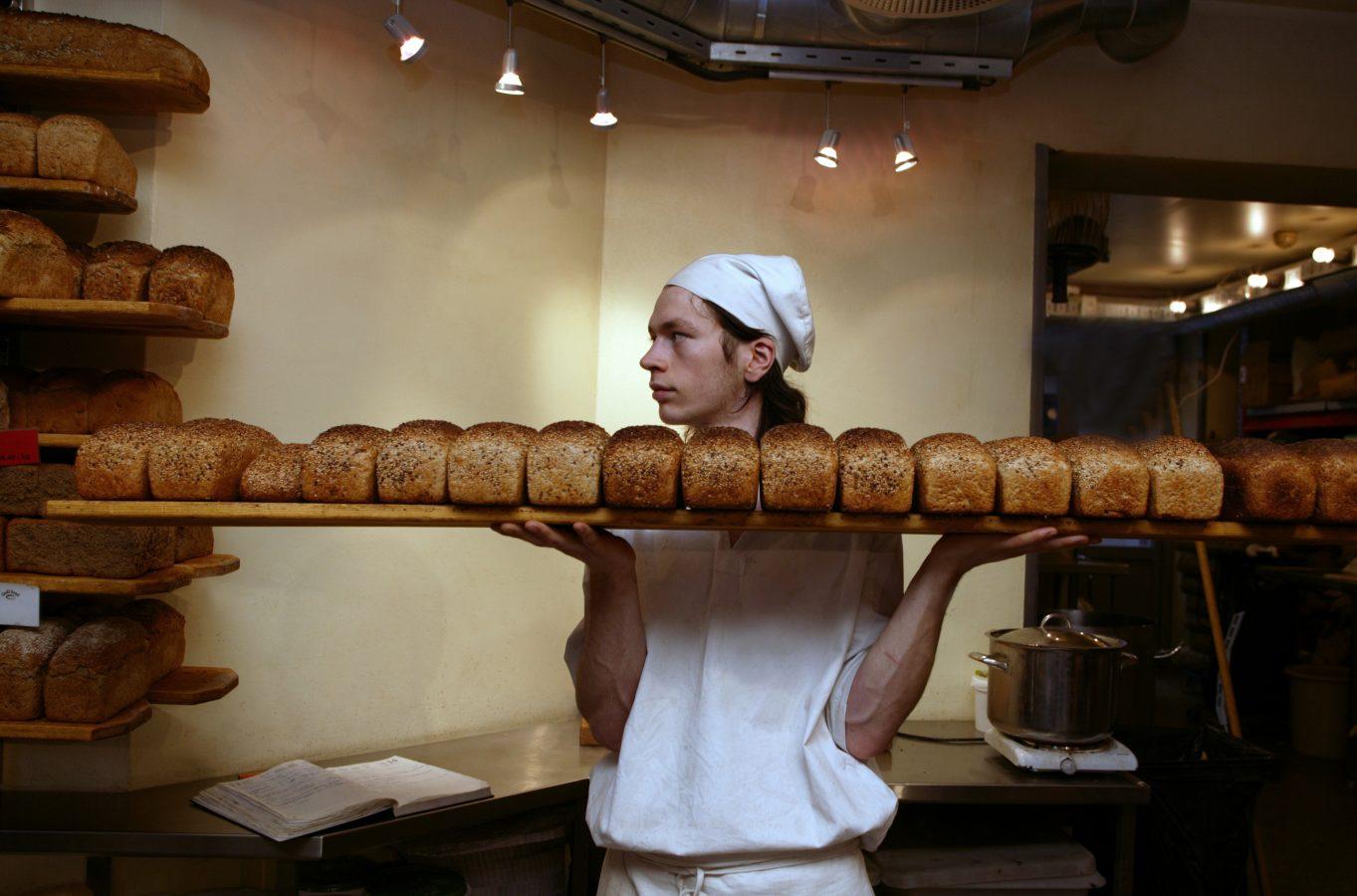 Ung mann tar et brett brød ut av ovnen. Foto: Berit Roald/ Scanpix ven.