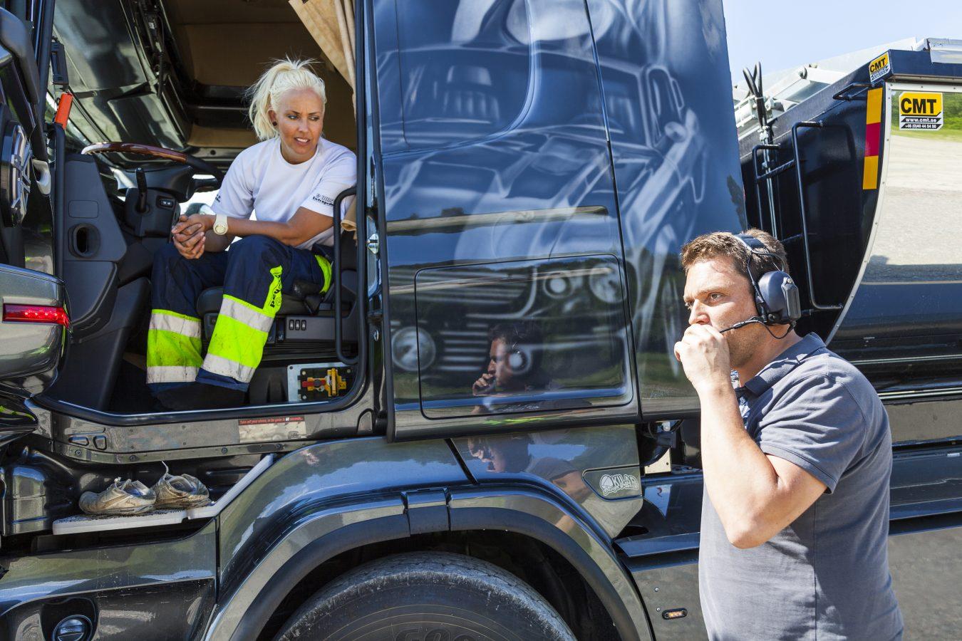 Kvinnelig lastebilsjårfør sitter i førersetet og snakker med en mann som står utenfor bilen.