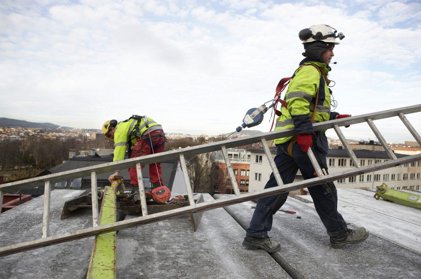 Person i arbeidsklær med stige i handa på toppen av et tak.