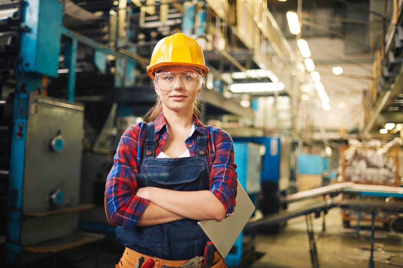 Portrett av ung kvinne i vernebriller i en fabrikk. Foto: Istock
