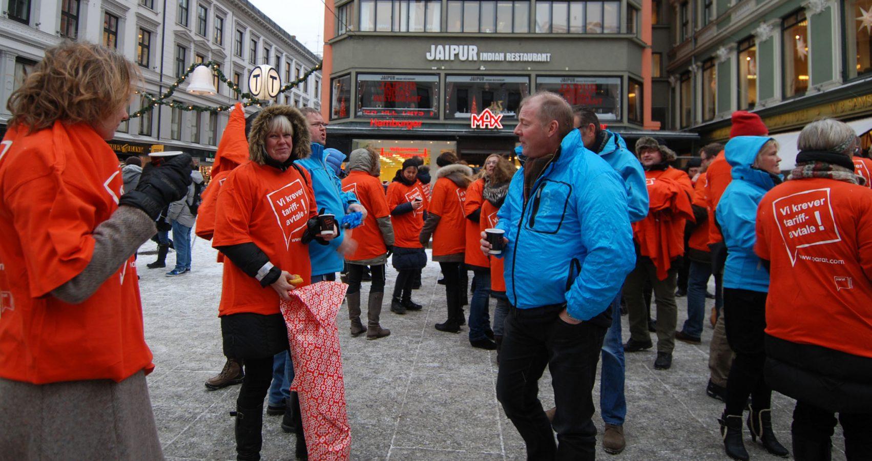 Mennesker med orane tskjorter med påskriften Vi krever tariffavtale er samlet på Egertorget i Oslo