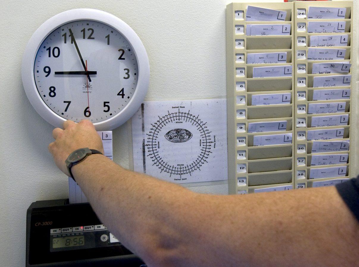En ansatt bruker stemplingsur. Klokke over stemplingsautomaten. Foto:  Gorm Kallestad/Scanpix