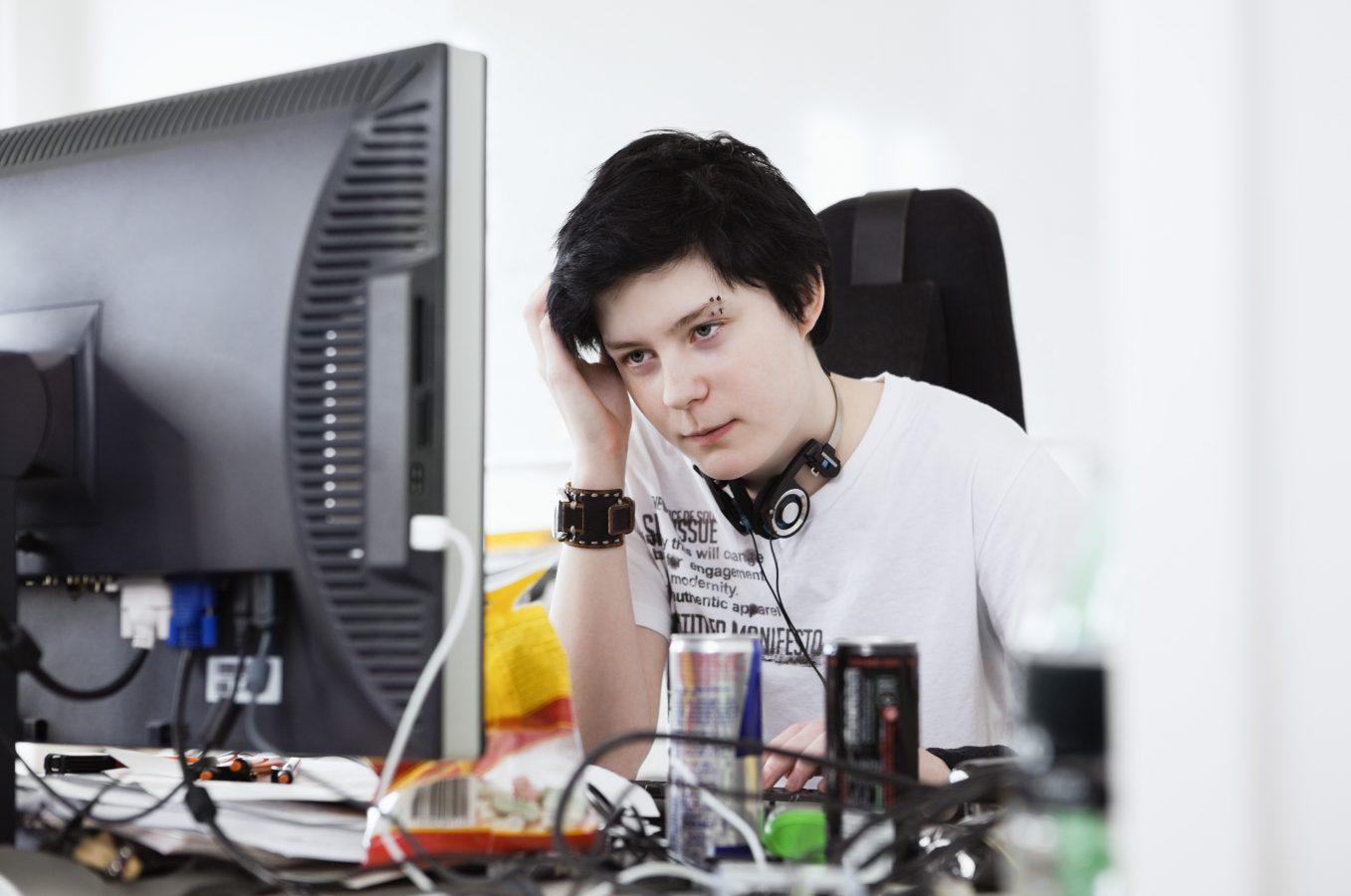 Ung kvinne sietter ved datamaskinen. Foto: Maskot