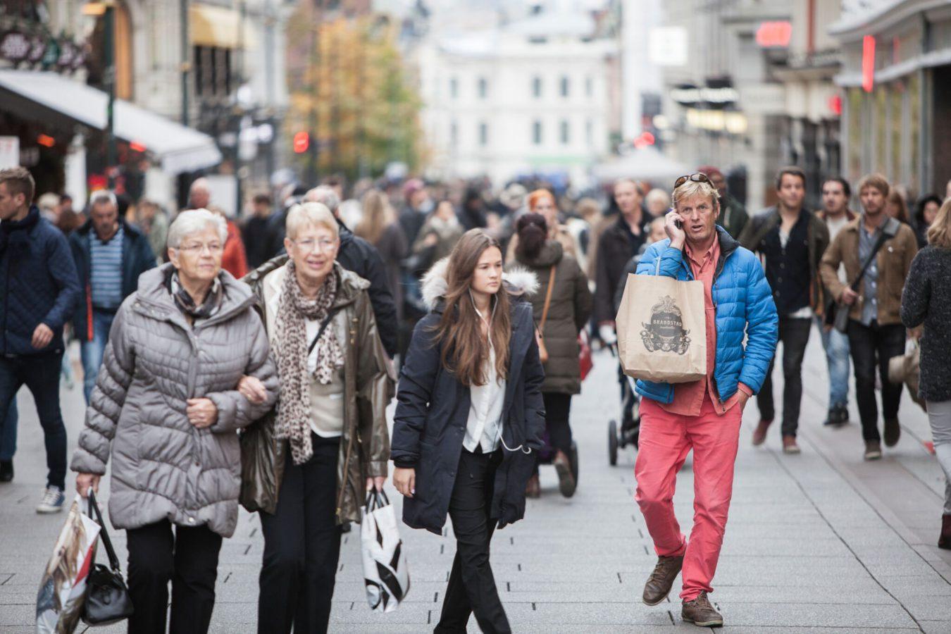 Folk går på Karl Johan. En mann snakker i mobilen, men en handlepose på armen.