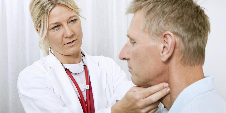 Doktor føler på halsen med to fingre.