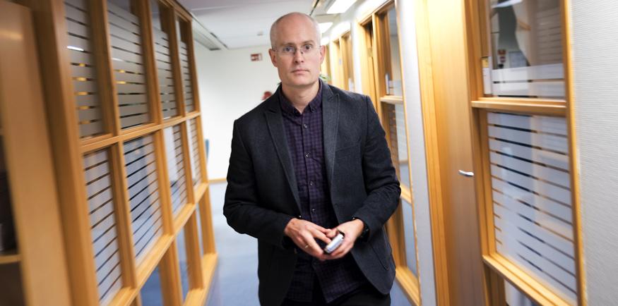 Forsker Anders Underthun står i en korridor med en telefon i hånda.