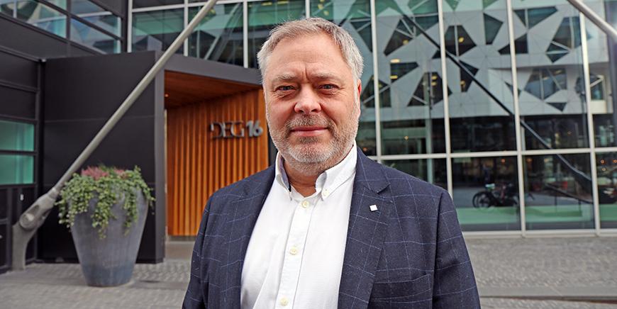 YS-leder Erik Kollerud står utenfor et bygg med mange små vinduer.