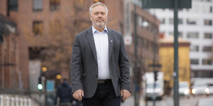 YS-leder Erik Kollerud med en rødbrun murbygning i bakgrunnen.