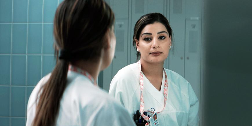 En kvinnelig helsefagarbveider står foran et speil og ser seg selv i øynene. Hun har hvite arbeidsklær på seg.