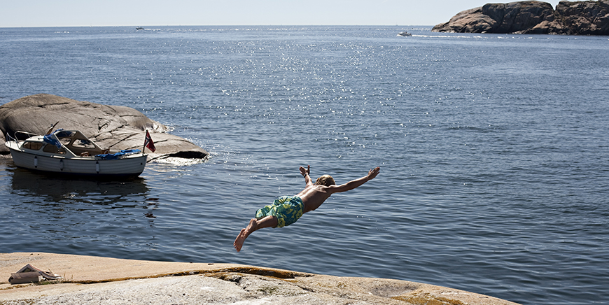 Young man diving from cliff, Vestfold, Norway