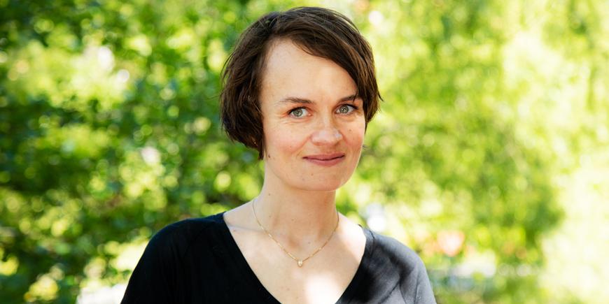 Portrett av Nina Skrove Falch mot grønn balgrunn med bladverk.