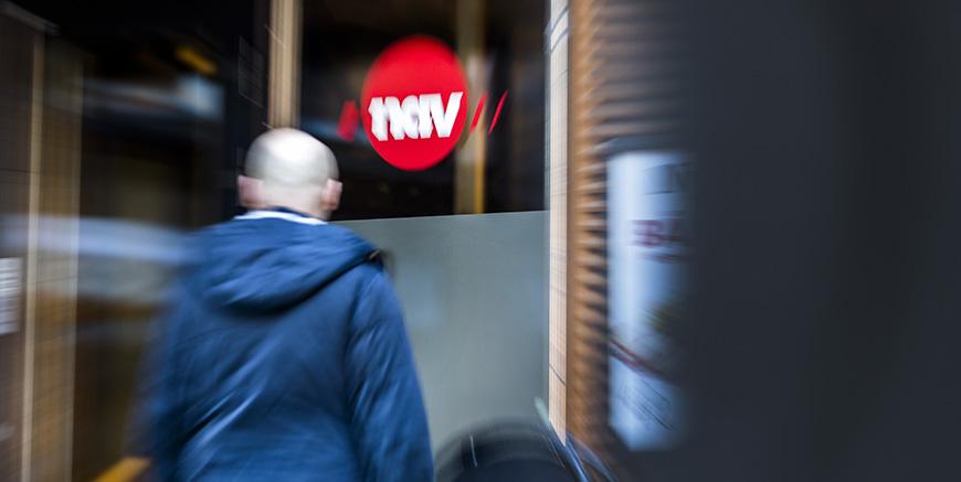 En mann utenfor med et NAV skilt.