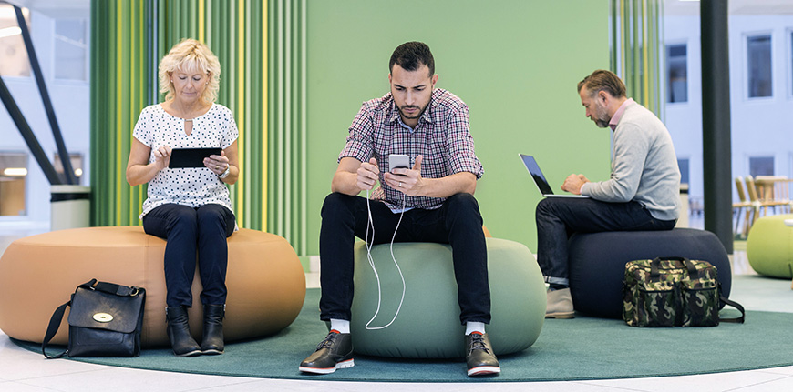 Businesspeople using technologies at modern office lobby