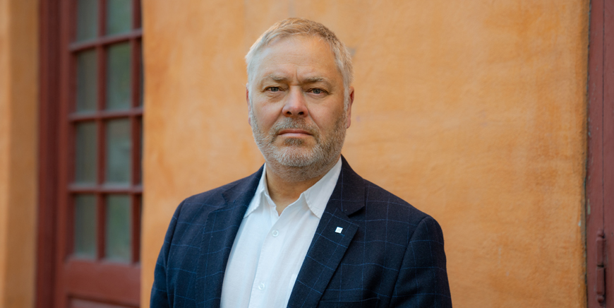 Portett av YS-leder Erik Kollerud mot orange bakgrunn.