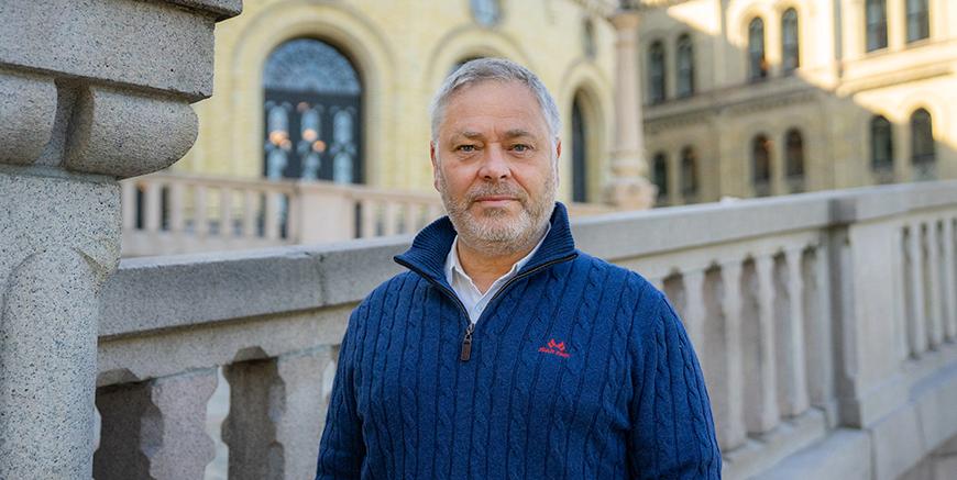 YS-leder Erik Kollerud, med blå genser, foran Stortinget.